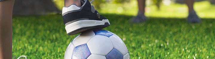 a close up of a game of kickabout on artificial grass in the garden - a football with a foot resting on top of it.