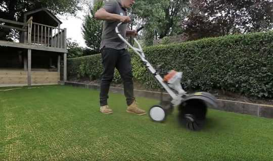 man power brushing artificial grass