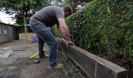 man installing timber frame for fake grass