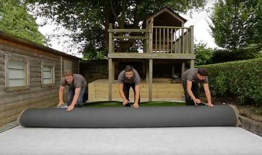 3 men roll out the fake grass ontop of sub base