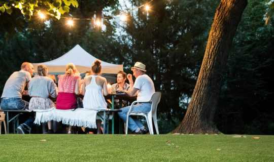 family dining on fake grass under fairylights