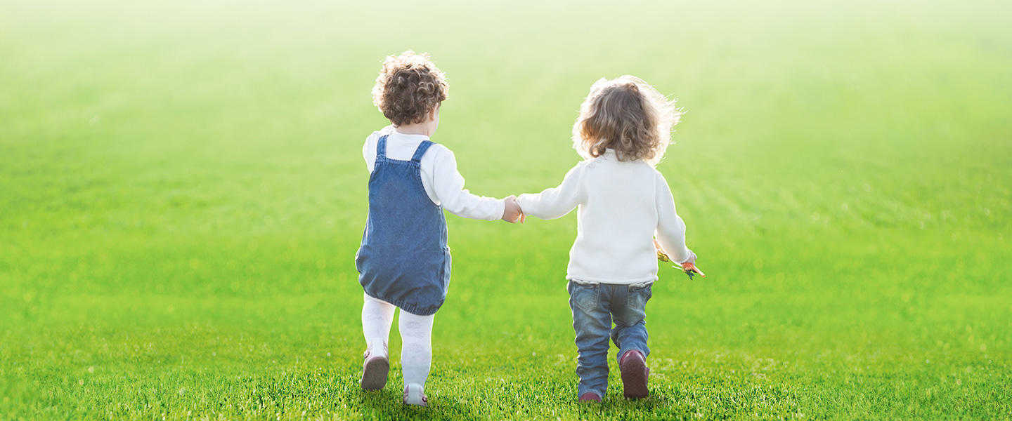 Children holding hands playing on fake grass